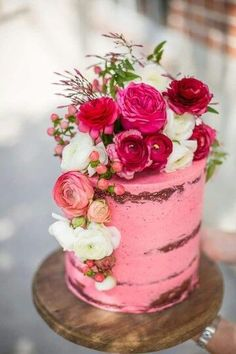 Un rosa fuerte cubre parcialmente esta torta de bodas coronada con flores frescas que hacen cascada a un lado.