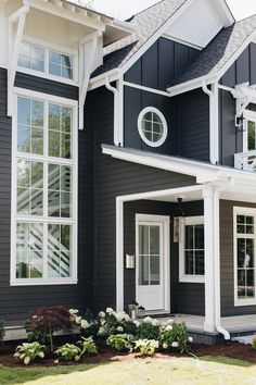 Navy blue home with white trim displaying glass windows and a lush front porch garden. Craftsman Exterior, Exterior Trim, Exterior Doors, Exterior Design, Stone Exterior, Dark Blue Houses, Dark House, White Exterior Houses, Exterior Paint Colors For House