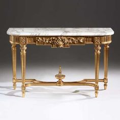 Carved wood console with floral motif, antiqued goldleaf finish and Calacatta gold marble top.