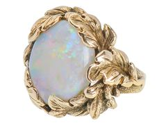 Nature's Realm - White Opal Ring. With an overall low profile, the magical gem is surrounded by a foliate wreath similar to those awarded to ancient Olympic victors. Realistically detailed, textured gold leaves crown the opal in an asymmetrical harmony of nature. Trumpet shaped shoulders embellished with texturing segue to a smooth silken shank. c 1940