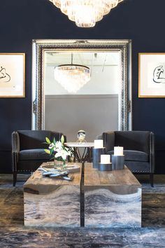 Navy living room features walls painted navy blue alongside a pair of navy accent chairs with silver nailhead trim flanking a round marble and iron accent table placed in front of a silver beaded leaning floor mirror flanked by abstract nude sketches.
