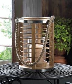 Light up your living space with a little waterfront style. This fascinating candle lantern features an interior hurricane glass to keep the flame of your favorite candle burning bright. The exterior features a wood frame with slender wooden crosspieces, metal banding and a thick rope handle at top.