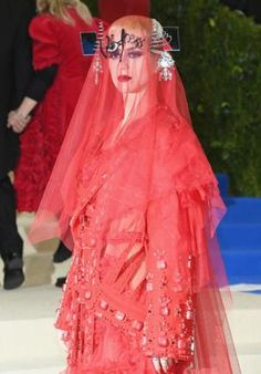 "Pop singer Katy Perry, co-chair of the ball, wore a red-tulle dress with a veil and the word ""witness"" across her forehead. She surprised some by wearing Galliano, not Comme de Garcons."