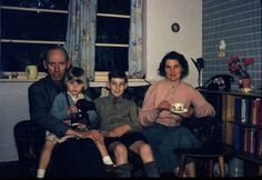 Printed colour photograph of Gordon Scagell, his wife Muriel and two children Andrea and Robin in the front room of 1 Milverton Drive, Ickenham, Middlesex. It was taken by an unidentified photographer on 14/05/1958. This is a copy made from the original colour Kodachrome transparency for the Geffrye Museum in 2009, and is one item in the Documenting Homes collection (150/2010-1 to –43) from Andrea Scagell. Object type: