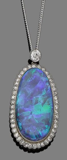 An opal and diamond pendant necklace, circa 1915  The oval cabochon opal, within a surround of single-cut diamonds, suspended from a brilliant-cut diamond, to a later flattened curb-link chain