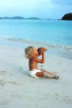 beach baby drinking from a coconut
