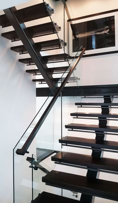 Modern straight staircase with glass railing.