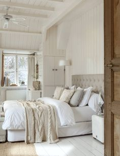 Dormitorio blanco y beige con paredes y suelo de madera blanca. Cama con cabecero tapizado en tono piedra. #elmueble #dormitorio #blanco #luz #decoracion
