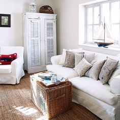 White loose covers on the sofa and chair keep the look informal, light and bright in the living room. Texture has been added with a spacious wicker storage box and natural flooring. The handy cupboard was made using old French shutters