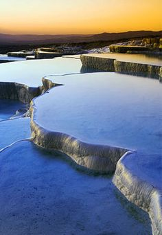 Pamukkale, Turkey  Cotton Castle, Pamukkale's translated name, is a wildly popular tourist site. Seventeen hot-water springs in the area spill out water in temperatures ranging from 95 degrees to 212 degrees, which contains a high concentration of calcium bicarbonate. The water flows off a cliff, cools and hardens into calcium deposits that form terraces, as white as cotton and bright enough to be easily seen from the town of Denizli, which is on the opposite side of the valley, 12 miles away.