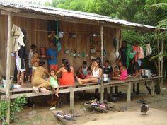 Eis a casa de uma familia na região Amazônia, Brasil. Parte dela aberta. Não há mesa nem cadeiras. Na foto, estão compartilhando uma refeição. Tudo se faz no chão, inclusive comer, e para isto se usam as mãos, não há talheres. No final, uma bacia para a lavagem das mãos.