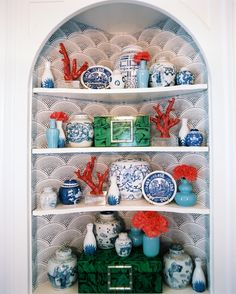 All-American Rooms in Red, White, and Blue: Punches of coral branches and a collection of blue and white china liven up a papered corner cabinet.