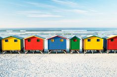 Tiny colorful bath houses dot the shoreline of Cape Town's St. The bold huts have been widely-photographed and are a popular tourist attraction. Read more at Discover Cape Town Saint James, James Beach, Bikini Rouge, Boulder Beach, Colourful Buildings, Colorful Houses, Beach Cottages, Beach Houses, Small Cottages