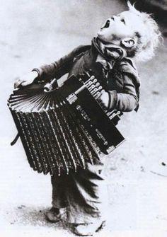 Kleine straatmuzikant zingen bij een trekharmonica.