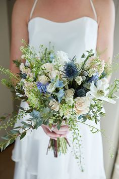 Blue thistles and white roses in a bouquet