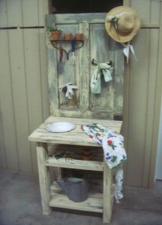 MY FIRST POTTING BENCH ~ I just finished my first potting bench!  I used an old door for the back and lumber for the rest and painted to compliment the door.  I cut a hole in the top to hold an enamel bowl.  I added a rake head shelf/hooks, spicket knob, and vintage sprinkler towel holder.  I think it looks kind of fun all dressed up.  Built by junkermidge