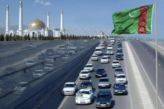 A wedding convoy passes a Turkmen flag near the mausoleum of the country's former leader Saparmurat Niyazov near Ashgabat February 19, 2009. REUTERS/Stringer