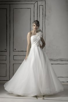 White A-line wedding dress with one-shoulder neckline and floor length. Oversized ornament accents the shoulder while satin is ruched throughout the bodice. Free made-to-measurement service for any size. Available colors seen as in Color Options.