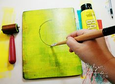 Balzer Designs: Roll yellow acrylic paint onto your Gelli Plate with a brayer. Draw into the paint with the back of a paintbrush or another blunt tool.  Press a plain piece of paper to the Gelli Plate and rub with your hand in order to create a print.   Be sure to clean the Gelli Plate afterwards with a piece of scrap paper.