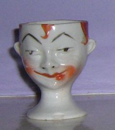 RARE CHINA EGG CUP CIRCA 1920/30. PIERROT FACE (after a fight.)