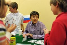 """Fifth grader Corbin Kroeker, 11, explains Slovenia's leading pastimes for second graders May 10 at Banning Lewis Ranch Academy in Falcon School District 49. While kindergarten-fourth grade students entered the academy's gymnasium, groups of fifth graders welcomed them to """"European extravaganza."""" They encouraged them to visit their country-themed tables, where they'd present research and stamp """"passports."""" The daylong event started with classroom presentations of slideshows and magazine…"""