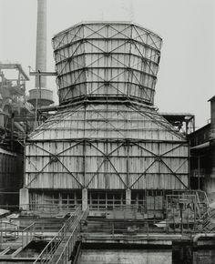 Bernd et Hilla Becher sont un couple de photographes allemands qui depuis les années 50 photographient des bâtiments industriels comme des puits de mines, des chateaux d'eaux, des usines ou des silos à grains. Leur particularité est de toujours les photographier avec la même lumière ( ciel couvert ), le même cadrage ( frontal et …