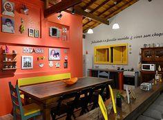 CASA DE PRAIA MERGULHADA EM CORES A sala de jantar, que é integrada com a de TV, tem mesa com cadeira de modelos diferentes e até um banco em um dos lados. Na parede, fotos da família e peças de afeto dão ainda mais personalidade ao espaço (Foto: Vanessa Bohn/Bohn Fotografias)