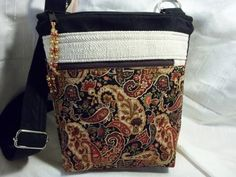 Crossbody V handbag in a black background with red,tan, browns paisley pockets and black body, with adjustable strap handle by ChickadeeHillDesigns on Etsy