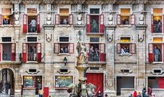 People mill around the doorways and windows of a building in Spain during an art exhibitio...