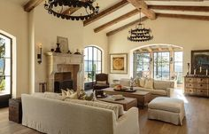 Mediterranean living room features cathedral ceilings accented with rustic wood beams and tiered ...