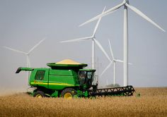 The ever renewable Iowa: A combine harvests soybeans that are used to make biodiesel and wind generators harvest the wind used to generate electricity. Iowa is a leader in the nation in many forms of renewable fuels.