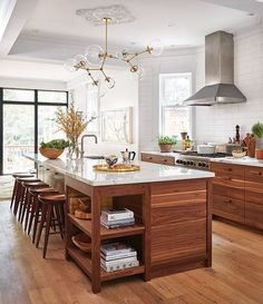 Vintage modern kitchen design featuring walnut wood cabinets, light gray and white quartz countertops, a large island with seating, and a contemporary brass chandelier - Kitchen Ideas & Decor