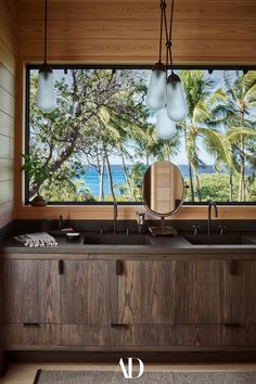 The bathroom of the primary bedroom features a postcard window that frames a quintessential Hawaiian scene. The custom stained-ash vanity with cast-concrete sink is purposeful but modest, a grounding, earthy element to anchor the view of sea and sky. #bathrooms #bathroomideas #bathroominspo #windows #palmtrees #views #sea #sky #hawaii #vanity #sink #concrete #wood #stained #custom #earthy Poured Concrete Counters, Concrete Sink, Polynesian Art, Secret House, Rural Retreats, Block Island, Visual Texture, Hall Design, Corrugated Metal