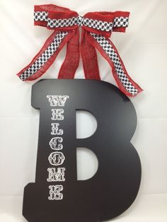 Black wood letter with Red Burlap and houndstooth ribbon bow. Great for the front door or inside decor. Perfect Christmas Gift! Choose your letter and we will fix it up for you. Several sizes to choose from. Call us 205 792 5659 Like us on facebook SHEILA's STUFF.