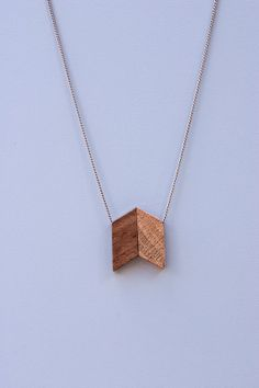 The geometric Walnut Tulip Necklace combines a style all its own with natural wooden materials. These gems salvaged in the making of furniture feature versatile tones and texture. Variations in material and shape should be expected from what is shown in the images as every piece is made by hand.