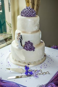 Very elegant 3 tier cake with purple flowers and white laces.
