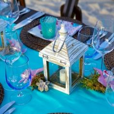 A beach reception complete with lantern and moss centerpieces and pops of color in Cabo.