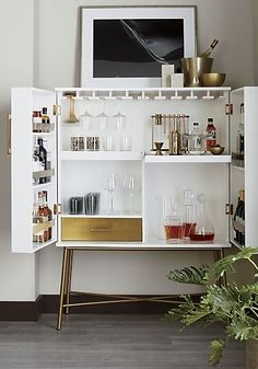 cocktail attire. The most beautiful bar in town. Elevate entertaining with sleek cabinet equipped for storing bottles and barware galore. Brass-plated metal legs and hardware warm a cool cabinet finished in hi-gloss white. Behind closed doors, discover shelves, notches for wine glasses, and a slide-out tray for cutting limes and lemons. Drawer offers space for stashing napkins, stirrers, and other accouterments out of sight.