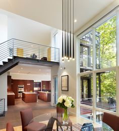 : Spacious Double Height Home Living Space Designed With Low Modern Chandeliers Above Round Glass Table