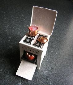 Super Cute Miniature Dollhouse Stove/Oven. (Dutch)  Wonder what those 'staples' are from. Look like jewelery link of some kind.