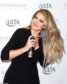 Little demo: The reality star spritzed one of her products on her golden locks...