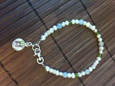 I made this bracelet for my aunts birthday. It's a mothers bracelet with her and her daughters' birthstones. It's made of sterling silver, fresh water pearls, peridot and aquamarine gemstone beads.