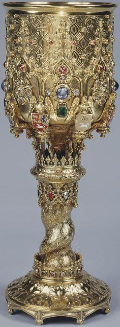 """Augustus Pugin 1827 Marea Britanie / Castelul Windsor / Colecţia Regală Cupă din argint aurit (a.k.a. """"cupa de încoronare"""") cu email, safire, smaralde, rubine şi diamante concepută (la vârsta de 15 ani!) de către Augustus Welby Northmore Pugin (1812-1852), executată de aurarul John Bridge (1753-1834) de la firma londoneză Rundell Bridge & Rundell. Achiziţionată în 1827 de către regele George IV. Înălţime 28,0 cm / diametrul la partea superioară şi la bază 10,5 cm."""