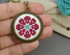 Round pendant with traditionally embroidered flower symbol. The cross stitch neck . - Round pendant with traditionally embroidered flower symbol. The cross stitch neck … - Tiny Cross Stitch, Cross Stitch Alphabet, Cross Stitch Flowers, Cross Stitch Designs, Cross Stitch Patterns, Round Pendant, Cross Pendant, Cross Stitching, Cross Stitch Embroidery