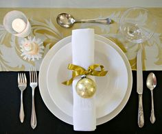 Classic Christmas For a more elegant Christmas place setting, stick with a single ornament and a subdued color scheme. Here, gold is showcased against white and elegant black. A gold ribbon and ornament are tied around a classic white napkin, which matches the table runner under the place setting.