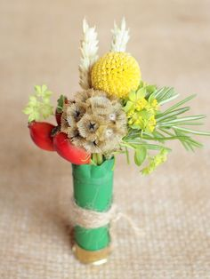 Country/farmer shooting inspired buttonhole, cartridge case with yellow craspedia, red rose hips, scabiosa seed head and wheat, finished with twine.