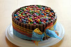 bake any cake you like, put on a generous amount of frosting. break kitkat bars in halves and glue onto frosting. tie and stabilize with a ribbon. fill center with m&m's and smarties.