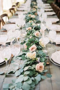 A runner of bay laurel, fern fronds, and silver dollar eucalyptus with scattered clusters of white delphinium, blush stock flowers, ivory spray roses, light blue delphinium with pillar candles and votives going down the length of the table