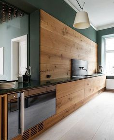 modern kitchen with sleek walnut cabinets and dark green walls …
