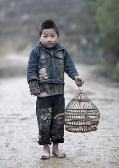 Hmong kid and his bird - Vietnam -   This little H'Mong kid was walking to his house with this bird in cage. I understood he bought it for Tet.   He wear a baggy jean, not for fashion, but cos he's too poor to have one which fits well...  Photo Eric Lafforgue